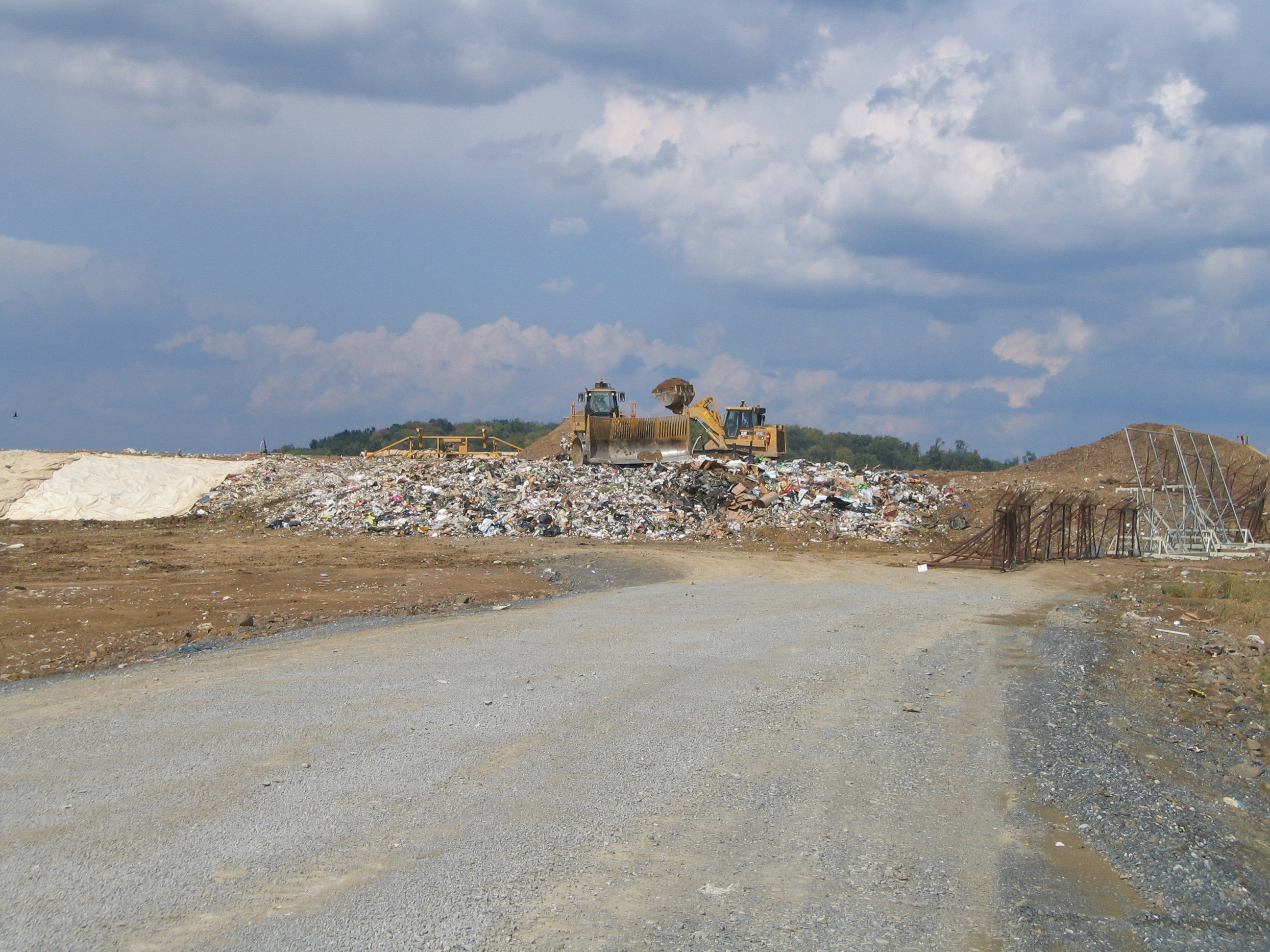 A bulldozer moving trash in the landfill