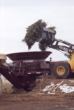 A tractor loading tree branches into a tube grinder